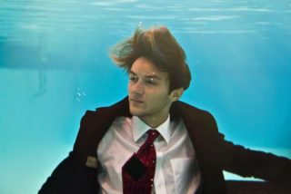 underwater shot of a young man fully dressed in a suit