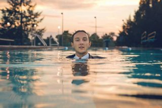 young man in a swimming pool fully dressed in a suit